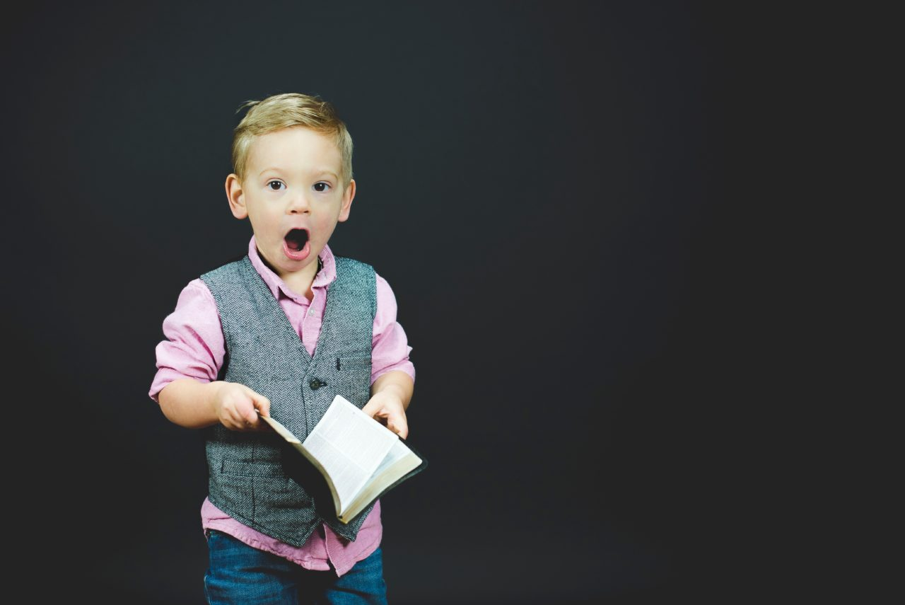 Shocked child holding a book
