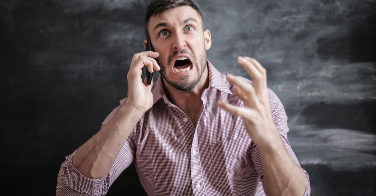 man in pink shirt angry on the phone